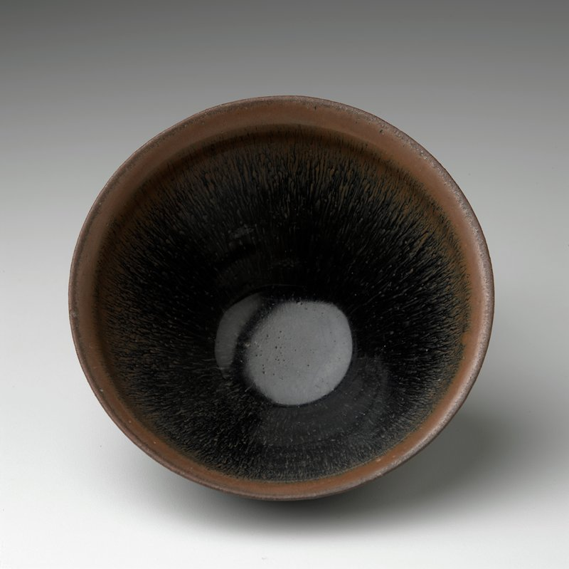 tall tea bowl with very thick glaze; unglazed foot; dark brown with light brown at rim; streaking down sides of interior and exterior