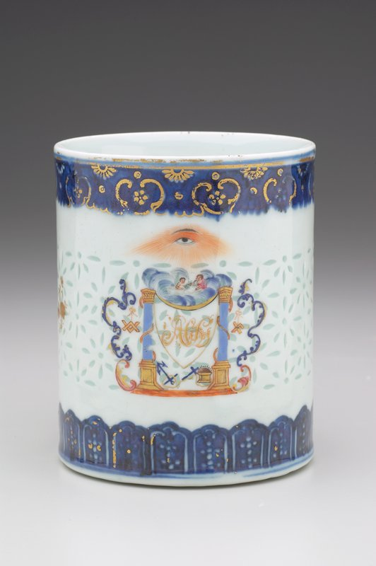 straight-sided mug with 2-piece entwined handle; pierced 'rice paper' ground; top and bottom edges and handle decorated with blue underglaze and gilt; area opposite handle painted with a shield surrounding a monogram with Masonic symbols; gilt flowers flank central design