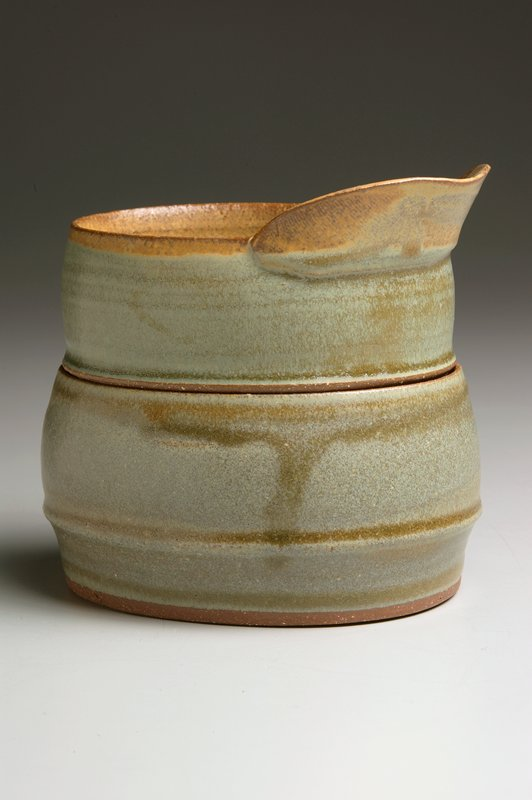 ovoid shaped with convex walls on each part; creamer with wide spout and unglazed bottom covers sugar bowl with unglazed bottom and rim; blue-green and light tan glaze