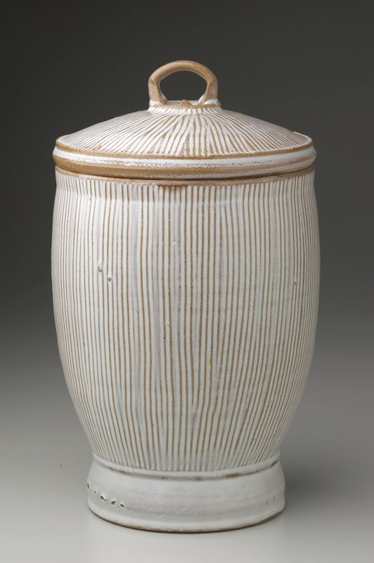 heavy, flat base slightly flaring outward; large mouth; interior and underside of lid glazed tan; body and lid decorated with vertical and radiating linear pattern respectively; exterior glazed white over tan