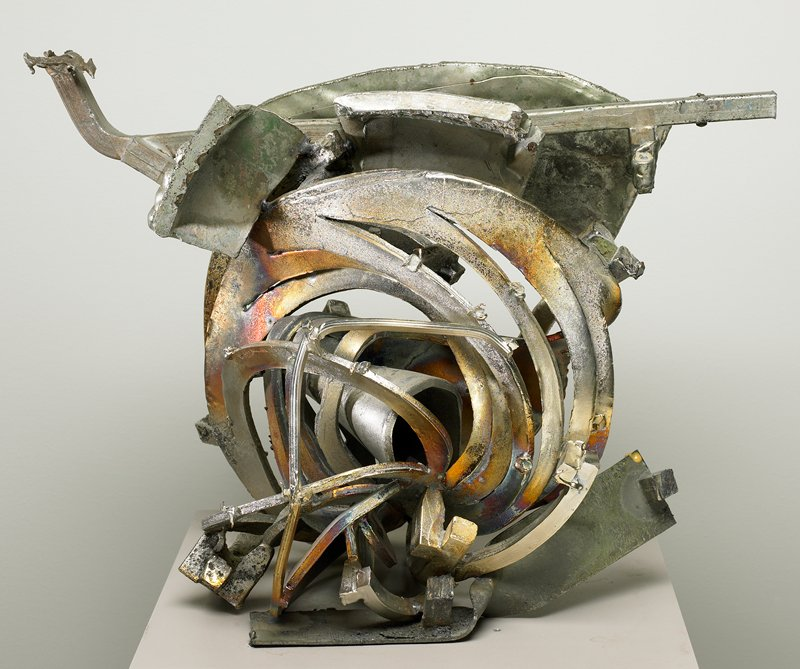 abstract sculpture with rounded section on bottom cut into parallel arcs and separated; horizontal bar at top with wedge-shaped plate on one side at top