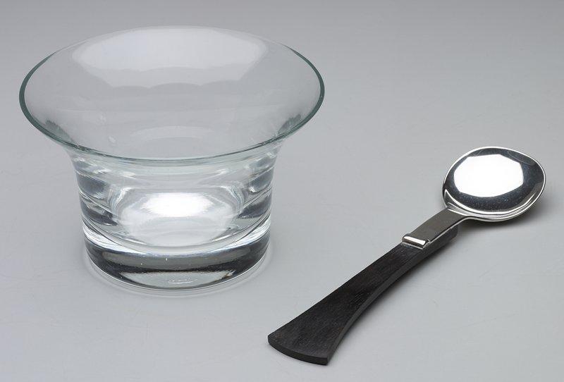 nearly circular bowl of silver; ebony handle flaring outward at end
