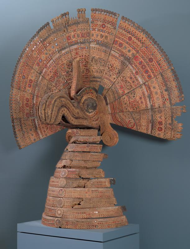 "half-conical open base made of bands of graduated sizes (breast of bird); head with large eyes and scrolling beak with headcrest and pair of ""ears""; fan of peacock-like tailfeathers; scrolling motifs and wheel-like roundels; brown, red, black, and white; received attached to small wheeled base with metal armature/stand"