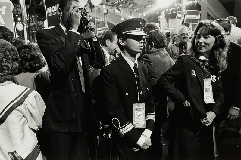 man, left, taking pictures, man in uniform, center, woman wearing button 'Women VP Now', right