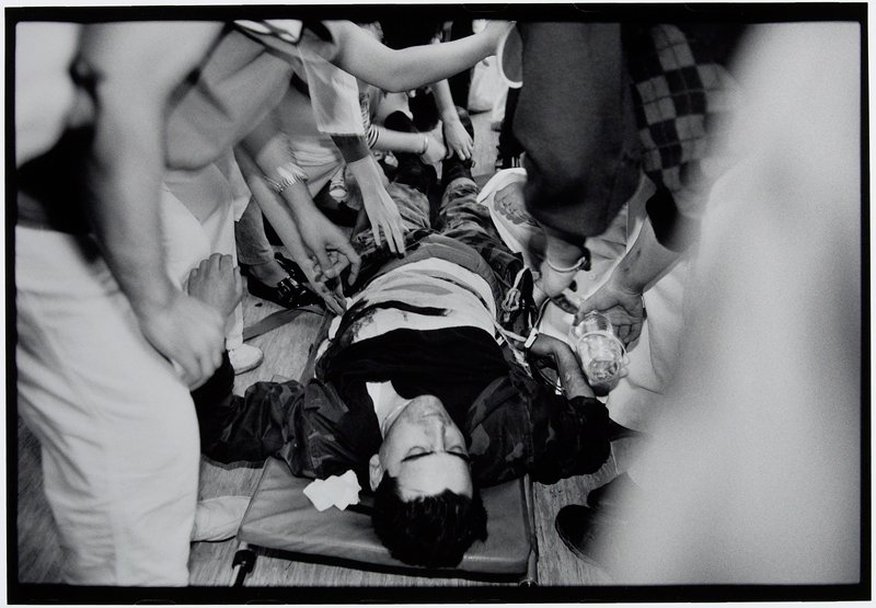 wounded man lying on stretcher with attendants on both sides