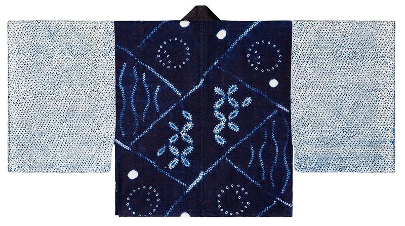 dark blue body with diagonal white lines creating diamond-shaped segments; segments contain various white patterns; black collar; sleeves have pattern of small dark blue organic shapes on lighter blue background