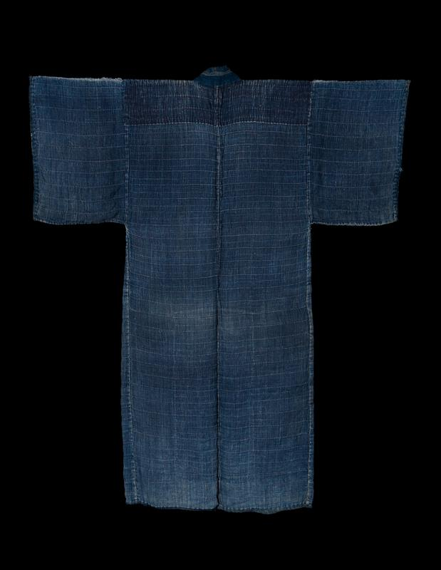 long blue coat with horizontal woven texture; dark blue fabric on shoulders and BC; solid blue collar; interior lined with various blue fabrics, patterned on front and lower back sections