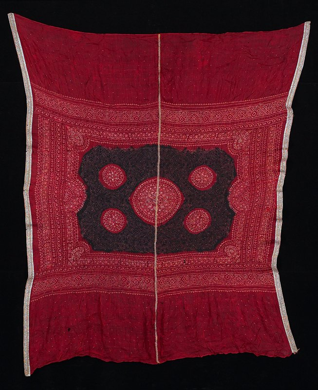 red background with central black area with 4 red circles; rectangular area at center has organic design made up of yellow dots; 2 hemmed edges, 2 edges have blue trim covered with metallic trim; small metal staples wrapped around fibers incorporated into design throughout; vertical gold braid at center