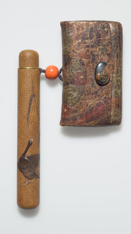 brown pipe case with woven pattern throughout; dark brown goose at bottom of case; reed on back side that moves upwards to front left side; leather case with decorative elements attached to case at the top with a brown, braided thread and orange stone/ bead in center; carved face on snap of the case