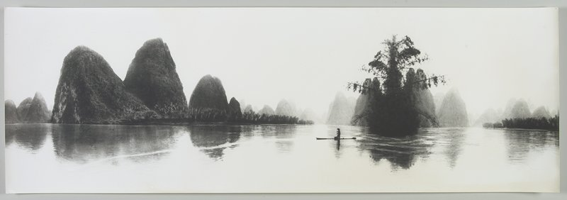 standing figure wearing a hat rowing a boat; foliage-covered land forms in background; tree behind figure