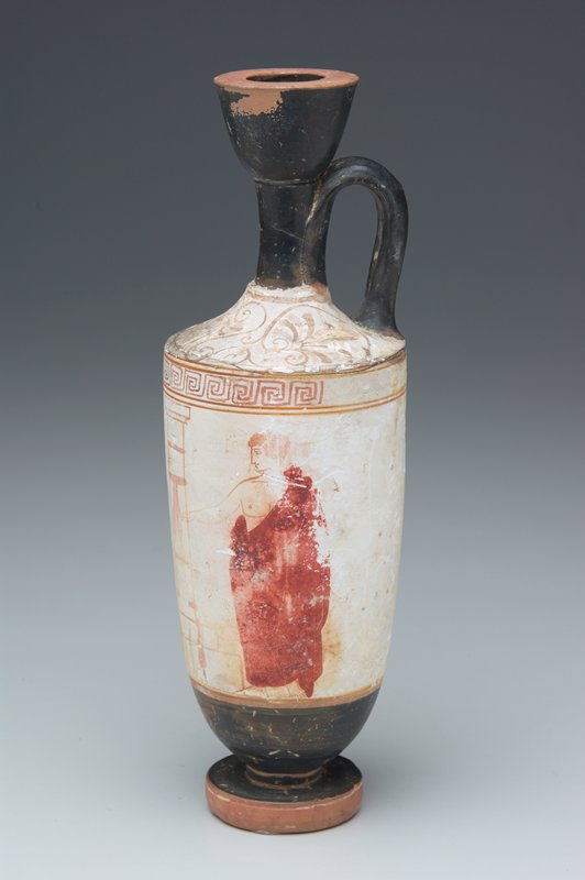 white ground lekythos, an oil vessel which would have been used in a funereal context; scene of maiden and youth in a red cloak, standing at a grave monument nude female figure to left and draped male figure to right
