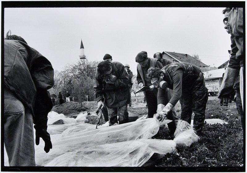 men wearing gas masks bent over opening body bags