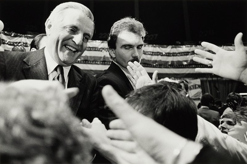 Walter Mondale shaking hands in a crowd at a political rally; close-up view of Mondale and body guard with eyes closed, hands extended out through bottom of image