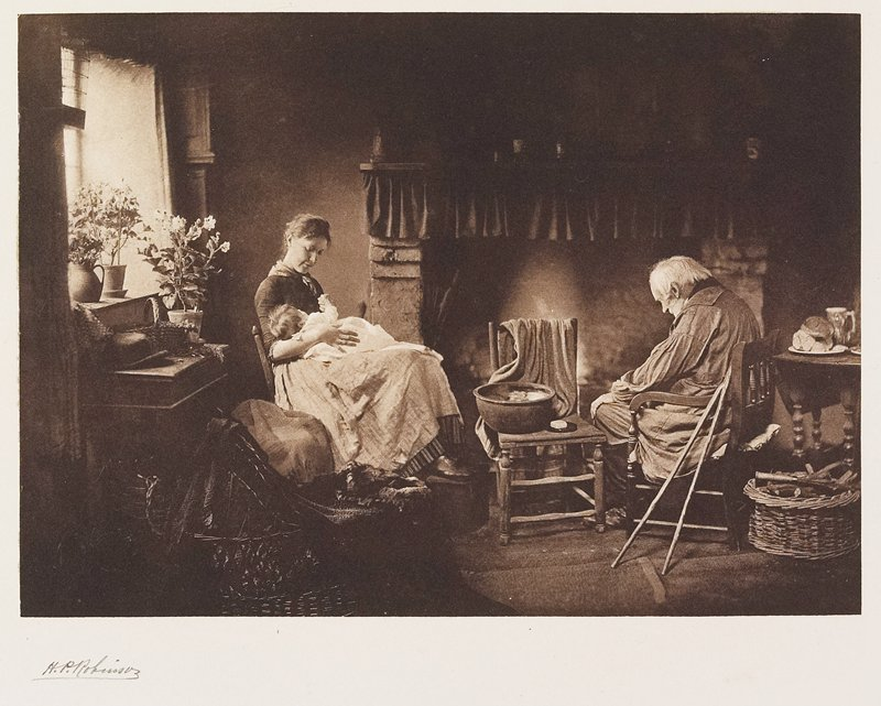 seated woman at L holding a baby on her lap; old man with head bent at R; fireplace at center; from a portfolio with essays on the photographer