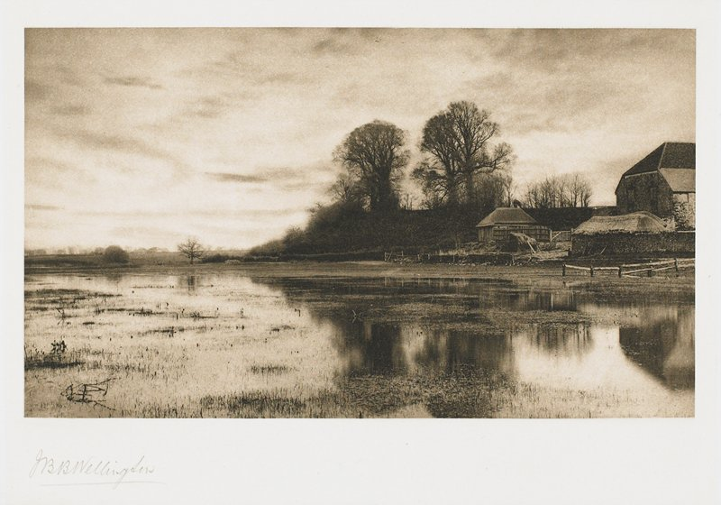 farm at R with large barn; shallow water in front with tall grasses visible; from a portfolio with essay on the photographer