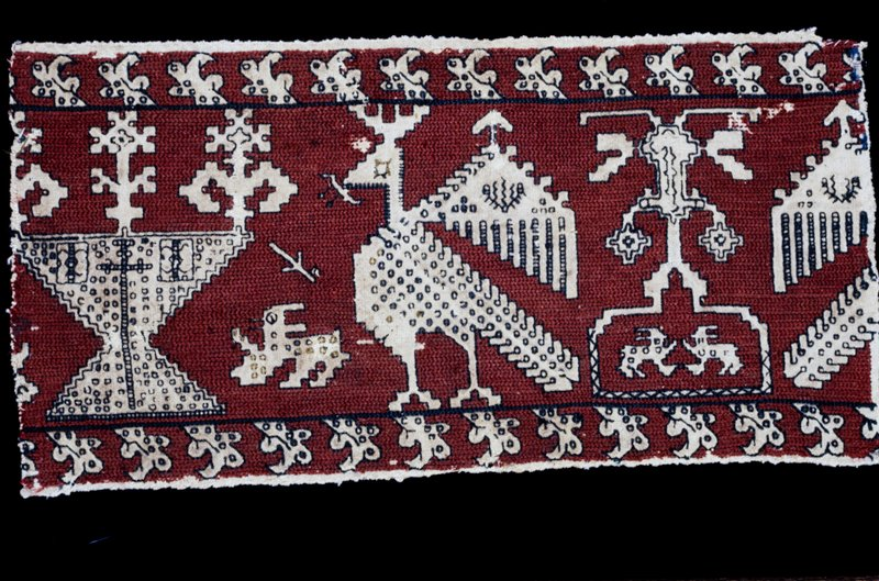 A border of linen embroidered with red silk background upon which birds fronting vases with plants (probably so-called tree of life) small animals and other fomrs are outlined in brown sillk (which may have originally have been blue stitches. Two outer narrow borders with leafy ornato. Design is evidently a repeated one, of which this specimen is half.