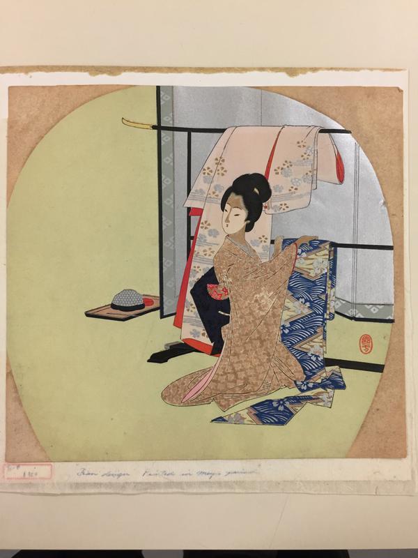 kneeling woman hanging up garments on a black rack
