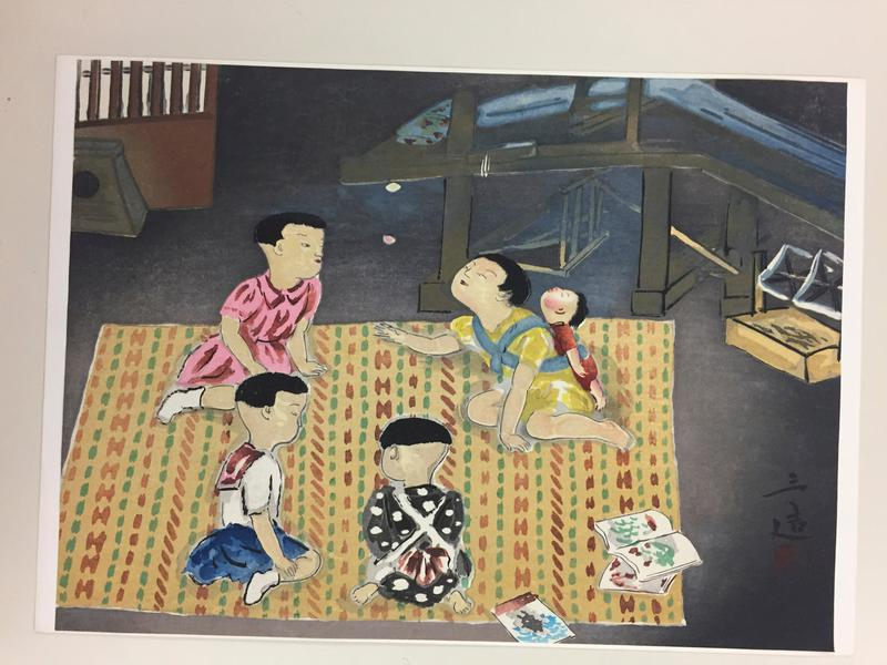 four children seated on a tan, rust, and green patterned rug; girl in yellow dress has a sleeping baby strapped to her back