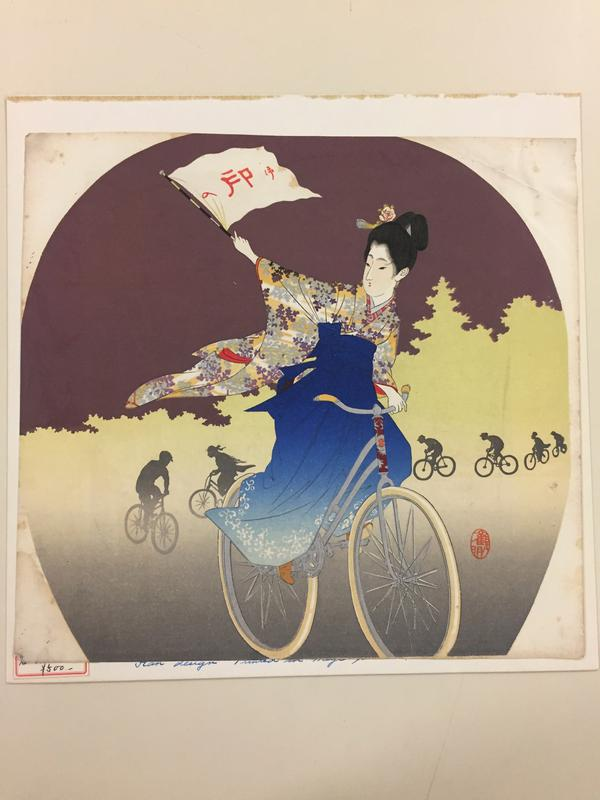 woman in kimono with blue skirt and flowered top riding a bike