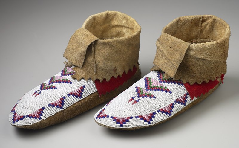 tightly beaded upper on top of foot with geometric design in pink, green, red and blue with white ground; red wool edge around heel