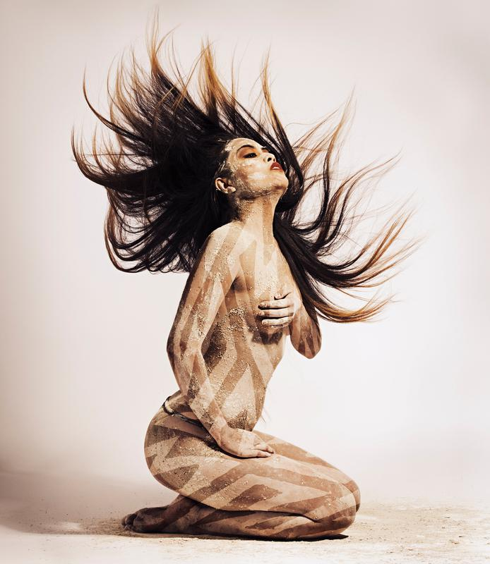 kneeling nude woman with brown linear marks and clumps of mud on her body, with her head upraised, throwing her long dark hair back