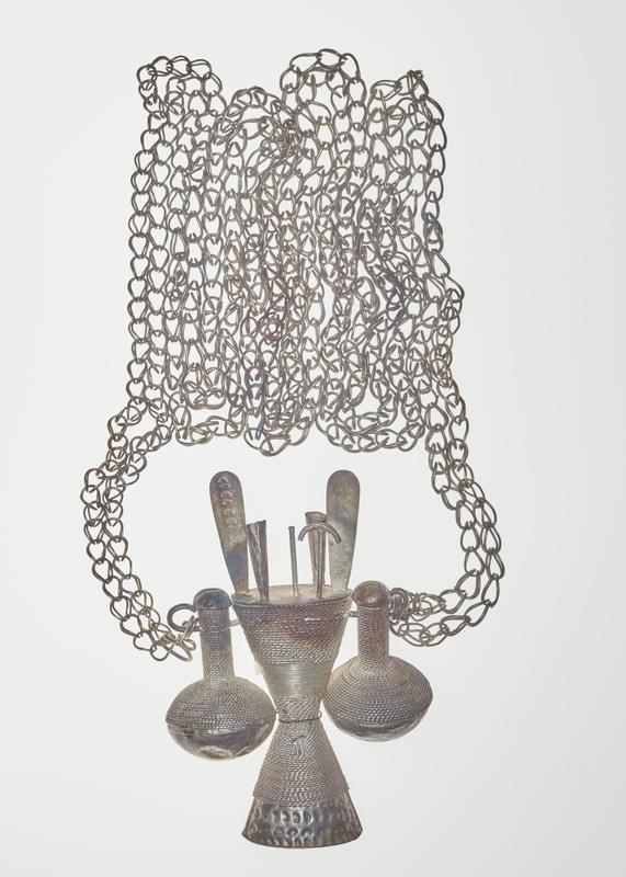 hourglass shaped centerpiece, wrapped in twisted trim, with six pieces coming out of top (two flats, two tubes, one stick, one stick with handle); two hollow side pieces also wrapped in twisted trim, with long necks and bulbous bases attached by post through top of centerpiece (one can swing freely, one is attached to center of centerpiece by wire); double strand, looped chain is attached at ends of post