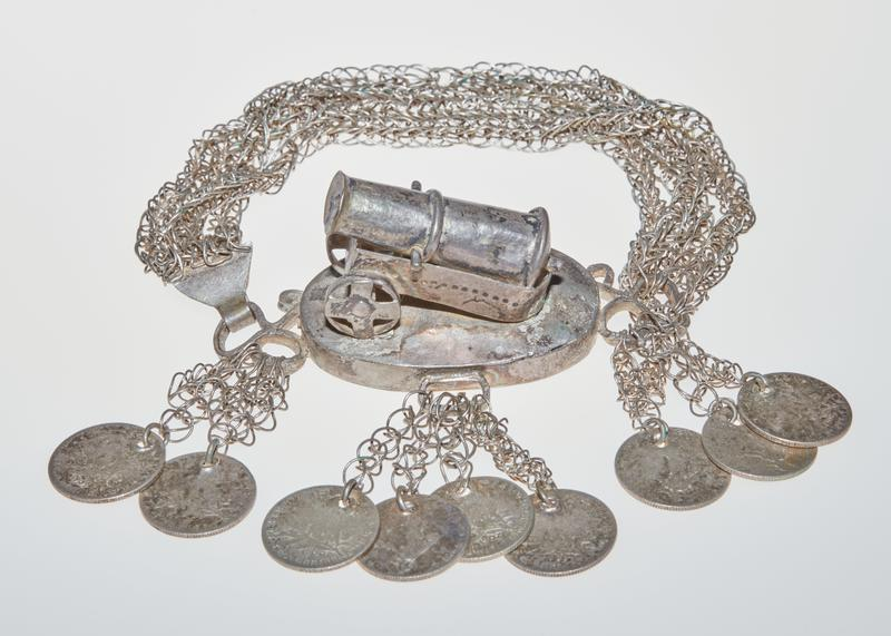four looped chains attached to ring on base of oval platform with hook on other side; cannon sits on platform with two front wheels and a base/cart with line of holes; nine 50 centimes coins hanging from rings around platform on looped chains (one set of two with two empty chains, one set of four, one set of three with one empty chain); all coins have a figure surrounded by text on one side and a branch of leaves with text on the other