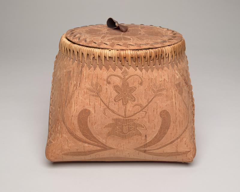 birchbark folded basket with lid; square base, circular opening, circular lid; light brown with darker brown designs: tulip-like flowers on sides, a deer on front, floral design on back; two areas of knots in wood on L side; stiches mending a vertical crack from rim to top of deer; panels secured on either side with straight stitches; looped stitches over rim; white, raw birch bark interior; flat lid with dark brown leather pull looped through center, tied to stretcher bar on underside; lid top decorated with floral design with triangular pattern around edge and straps attaching bottom lip worked into triangular pattern