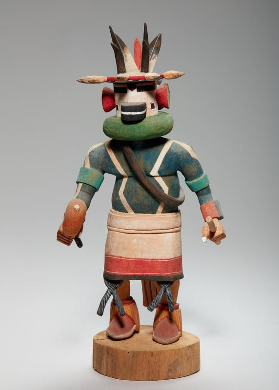 carved, painted figure, leaning slightly forward with an object in each hand (flat, round object on stick in PR hand; longer stick in PL); face with black beak and circular black eyes; visor-like headpiece with tan seed-shaped points, painted red with white zigzag on top and striped red, orange, and green on bottom; red funnel-shape ears, with orange and green segmented pattern on outer side; 2 black antlers on top of head; black-tipped feathers at back of head with one red feather; green neck piece, black sash over blue chest with white lines; tan, red and black skirt with tan tail on backside; black ties at knees; red boots with light brown fringe at ankles; figure standing on wood round