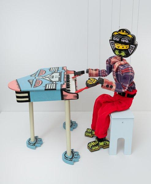 piano playing marionette; marionette has wooden shoes, hands, and head, all painted black with yellow, pink, and green designs, and is dressed in a blue and red plaid shirt and red pants; each hands has a red toothbrush attached with fishing line; each shoe has a square metal piece attached to toe (similar to tap shoes); light blue piano bench; blue toy piano with pink, black, and light blue designs resembling a face with the keys as teeth; piano legs are pale green with blue and black feet resembling paws; black marionette strings attached to either side of head, both shoulders, both wrists, and one on back