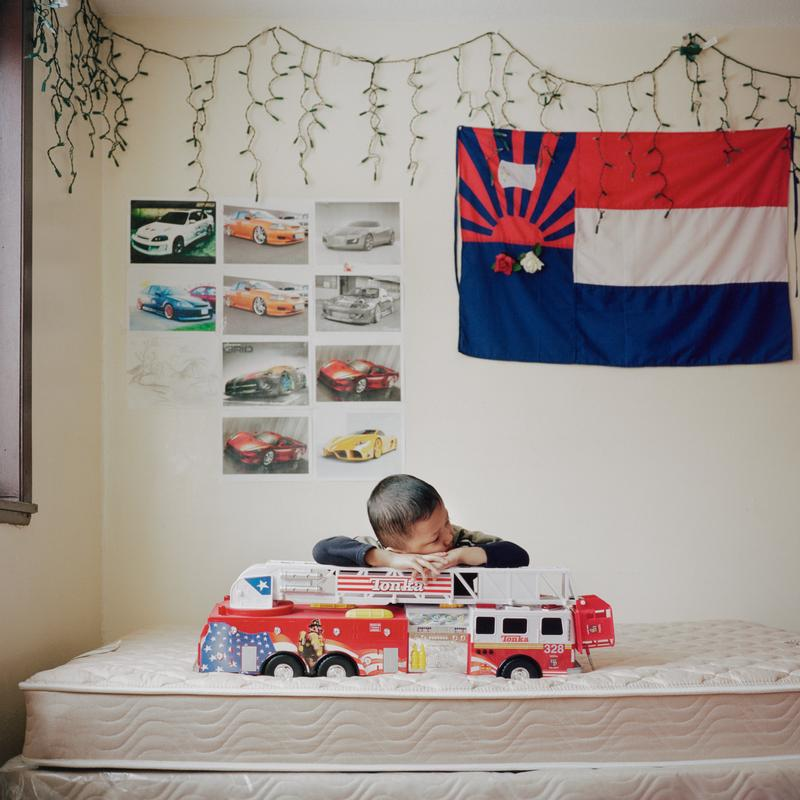 image of a little boy resting his head on his arms on top of a large toy fire engine on a bare mattress; red, white, and blue flag on wall at right with a rising sun in UL and three bold stripes; pictures of sports cars on wall to left; icicle Christmas lights above flag and pictures of cars