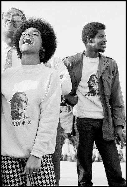 "black and white image of young woman with Afro hairstyle, with her mouth open wide, wearing a sweatshirt printed ""MALCOLM X"" with his portrait, and houndstooth pants, at left; young man at right with head turned to PL, smiling, wearing identical sweatshirt, jacket and black pants; received in black frame"