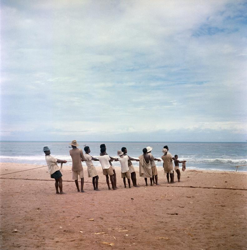 Color photograph of figures standing on a beach pulling a rope