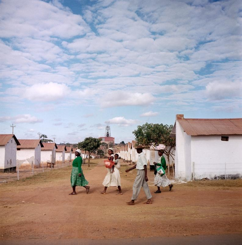 Color photograph of a small group of people walking across the road with rows of white buildings on the background