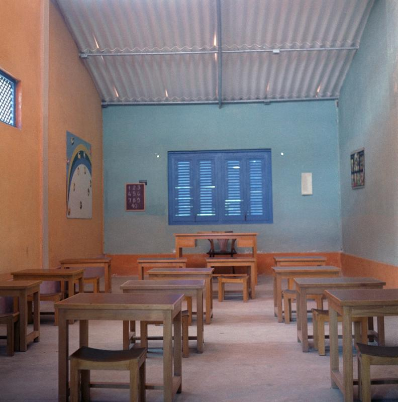 Color photograph of an empty classroom with teal and orange walls