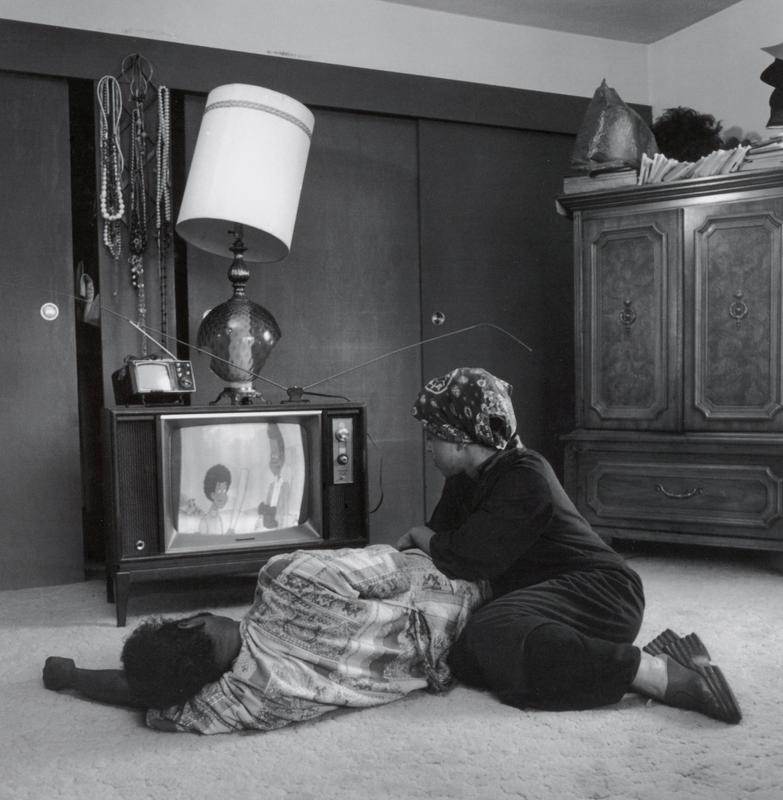 black and white image of a Black couple on the floor in front of a console TV with a lamp and a smaller TV on top of it; man lying on his side, wearing a patterned shirt; woman wearing a dark colored outfit and a patterned headscarf leans over man