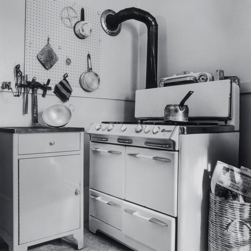 black and white image of a large cooking stove with four warmers and a small cabinet; pans, hot pads and tools on wall