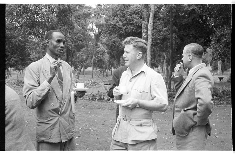 Black and white image of figures standing outside; two central figures drink tea and one smokes a cigarette