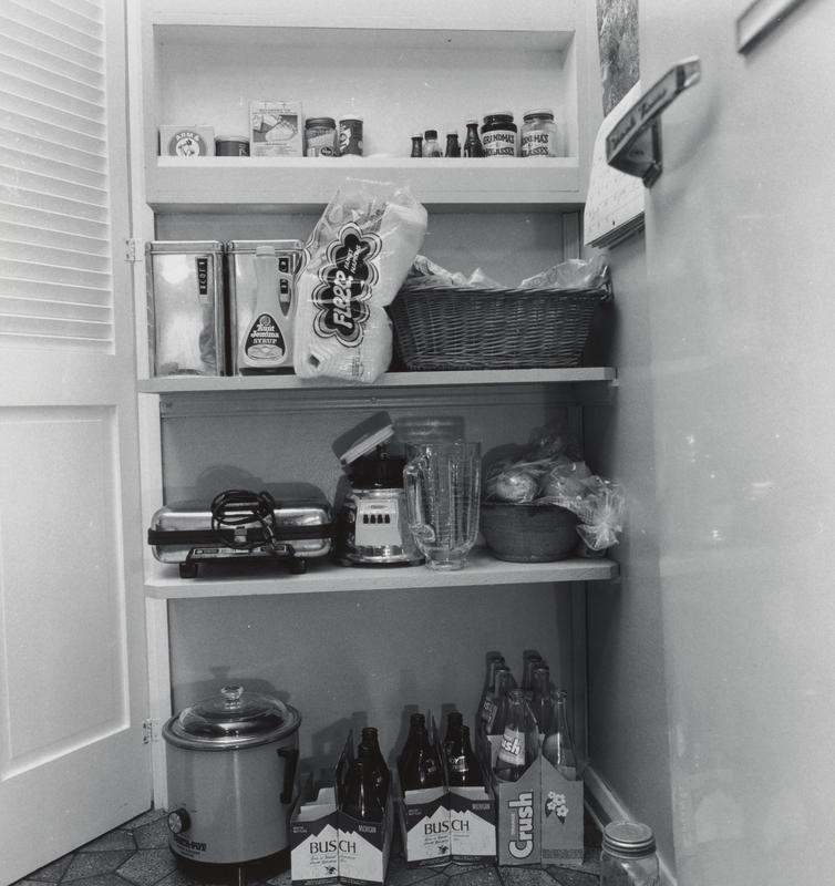 "black and white image of shelves in a kitched with Crock Pot, blender, waffle iron, basket, napkins, and empty bottles of Busch beer and Orange Crush in paper cartons; same room as in image titled, ""Pantry Shelf, Ruth's Home, Pomona Road, Ann Arbor, MI"", but slightly different vantage point (.55); nearly idential to .64 (cropped slightly differently)"