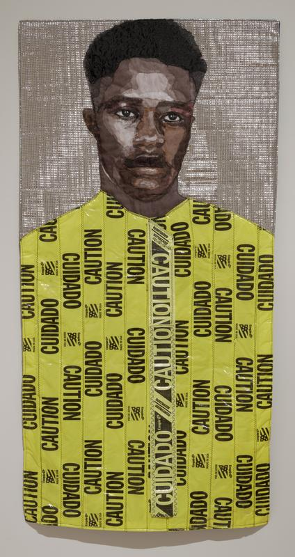 image of a Black man on a silver ground; his shirt is made from yellow and black plastic caution tape arranged in a vertical pattern; piece of caution tape at center is intentionally loose; rod pocket for hanging