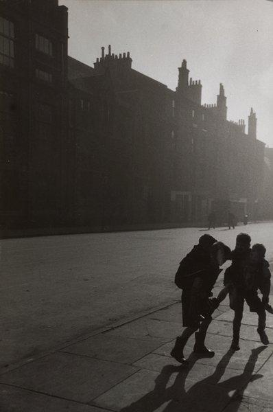 black and white image of four boys with two boys each carrying another boy piggyback on a twilight street; tall buildings on opposite side of street from boys