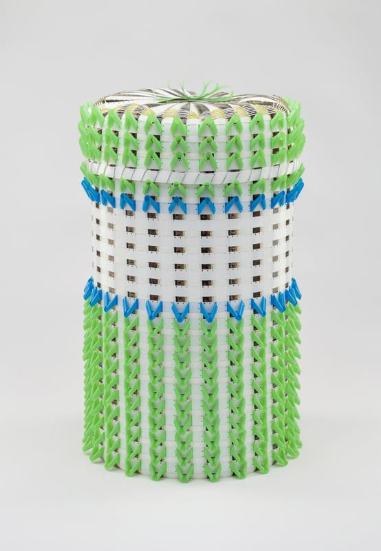Large, cylindrical basket made out of 16mm film in white, blue and green; plexi cylander stays on interior for support