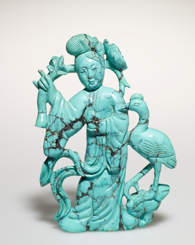 Figure of a lady holding peony tree with a flamingo on right; Turquoise matrix elaborately carved; wooden standard,(located at A10.7 MS)