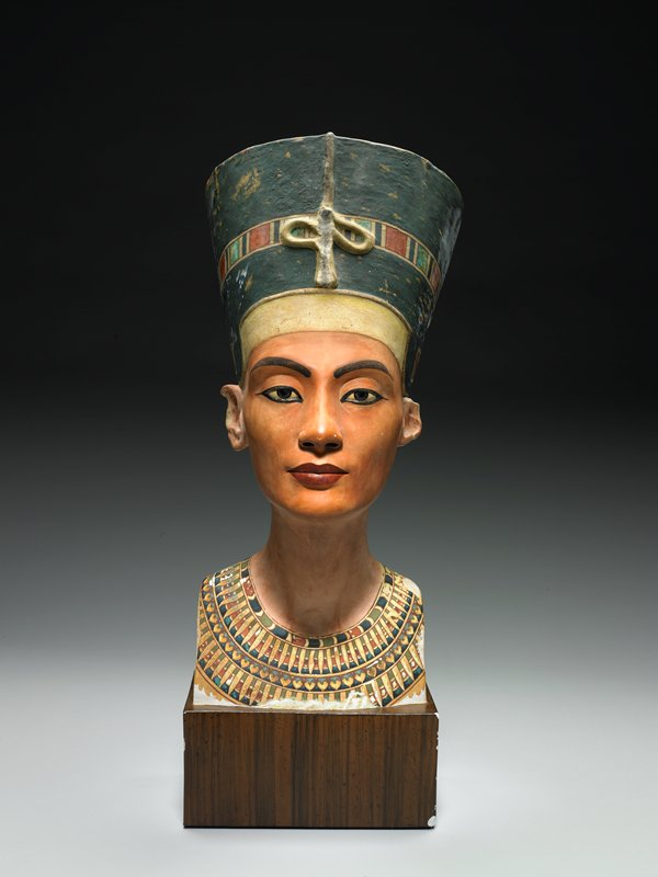 Bust of Queen Nefertete, colored, facsimile of painted limestone portrait head in the Neues Museum in Berlin.; Original of this bust was found in the studio of the sculptor Thutmose at Tell el Amarna, in 1912; attached plaster base looks like wood.;
