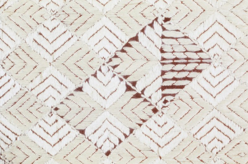 Panel of dull red cotton material embroidered in an all-over pattern of diamond shapes in stain stich worked in white silk. At both ends are borders of diagonal bars of diamond shapes embroidered with orange silk.