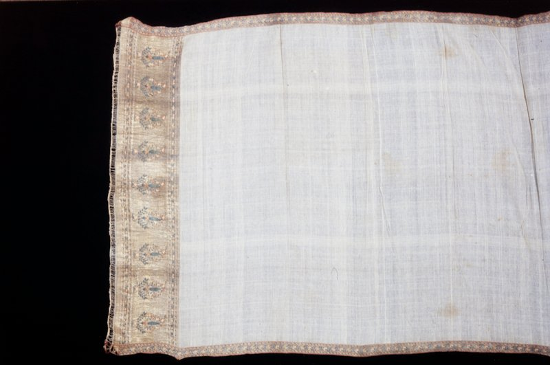 Short sari of white cotton material with borders woven in gold and colored silks added at both sides and a wider silk and gold border at each end decorated with nine palmette patterns.