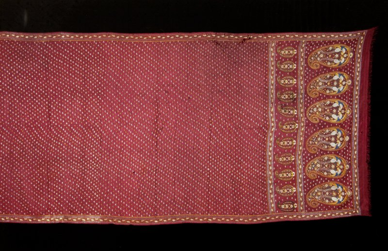 Sari, dull red silk. Embroidered with rows of small yellow and white flowers. Narrow border on each side and very wide border at each end of two bands of palmettes, the lower consisting of six palmettes, and the upper band of eleven palmettes. Very long.