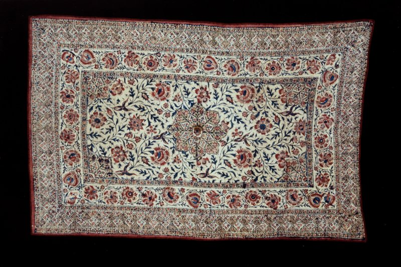 Cover, block printed cotton. Naturalistic flower and vine pattern in center panel and border. Dull red and blue dye on cream ground. Red lining. Cotton.