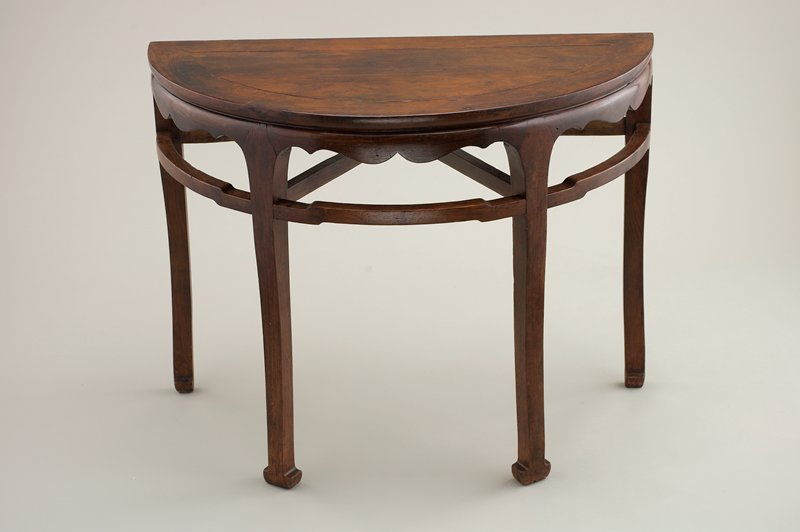 half-circle table with 4 legs around rounded side; short barbed apron on front with curved supports below connecting legs