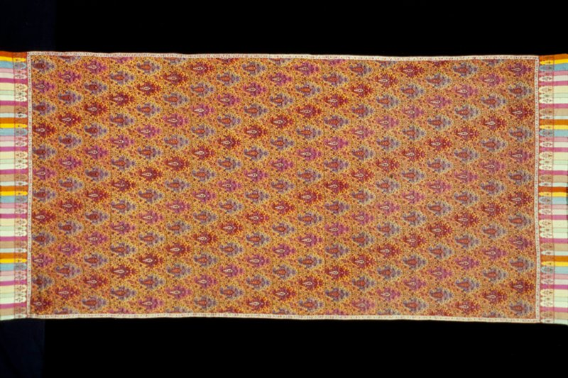 doshalla or long shawl with a yellow wool ground completely covered with Butha and intricate thal; border at each end woven on a vari-colored striped ground containing floral and basket design; narrow border on white ground is applied at the sides and set off the end border; this shawl is the same on both sides and the design is entirely outlined in embroidered stitch; alike on both sides
